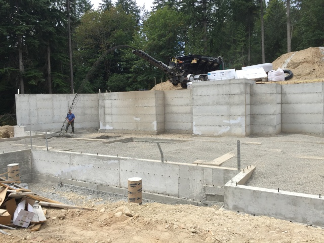 Here they are adding more gravel for the base material (and for drainage underneath the basement slab).