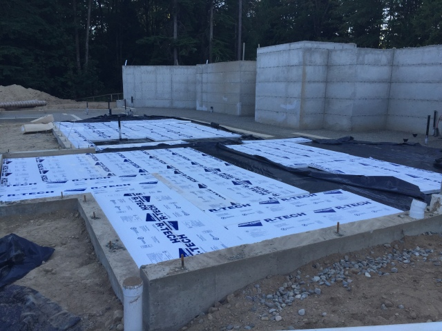 Here you can see the vapor barrier (black plastic) and a bit of the rigid foam insulation which is installed underneath the concrete slab.  To meet King County's energy codes, we opted to install R-10 insulation underneath our entire slab.  That'll also help keep the boys' toes toasty in the winter.