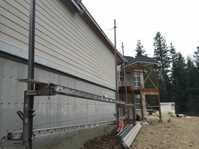 The top part of the garage has siding, but they still need to work on the part below the belly band.