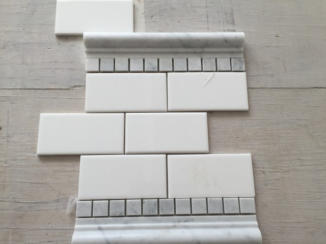 "The detail band in the master shower will be separated by a cararra marble chair rail and a row of 1"" cararra tiles."