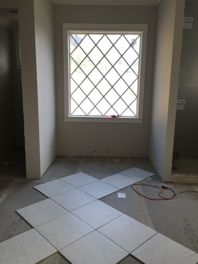 "In the master bath we decided to turn the floor tiles ""on point"" which mimics the window grids.  This was just a dry run of it, but I have a hunch that it'll look great!"
