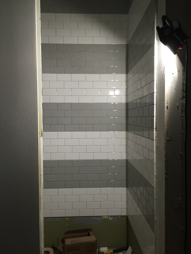 In the guest bath shower we had them create stripes of gray and white subway tiles and 1' each. I absolutely love how this is turning out!
